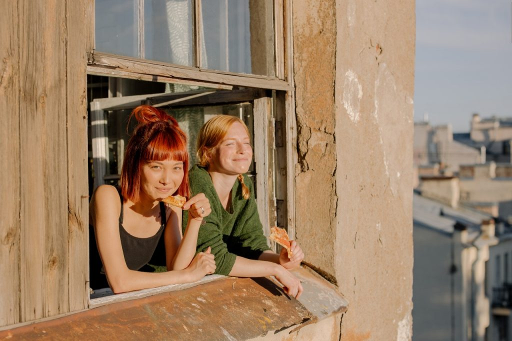 students-smiling-in-open-window-sunset